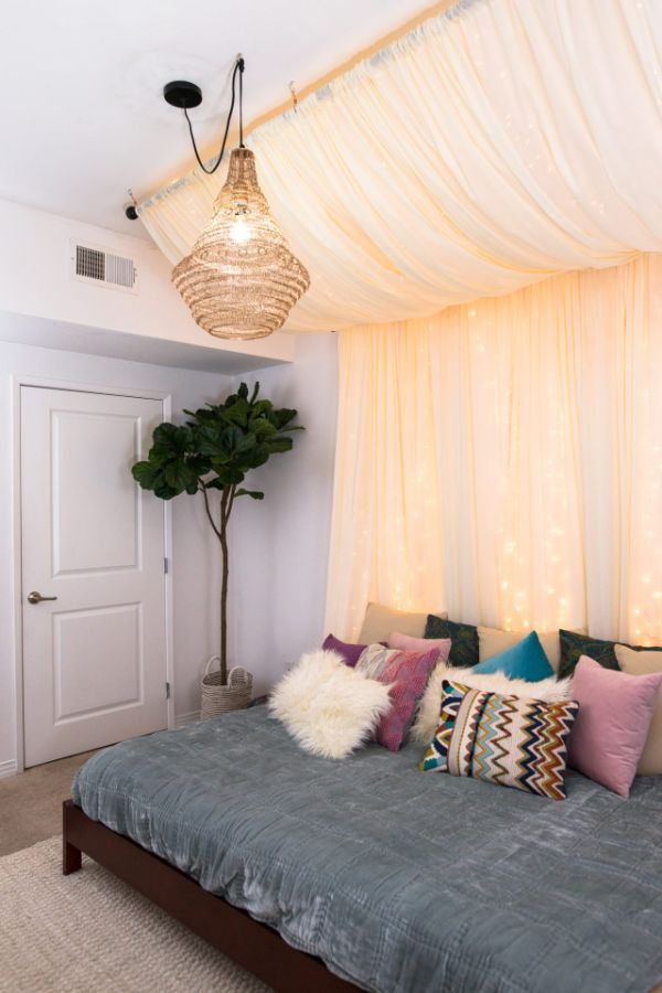 Curtains with fairy lights as headboard backdrop
