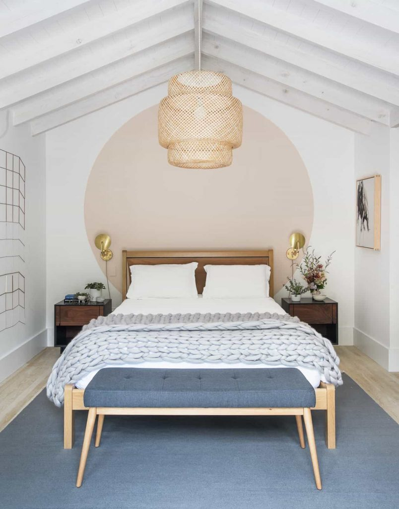 scandinavian bedroom with painted circle behind bed