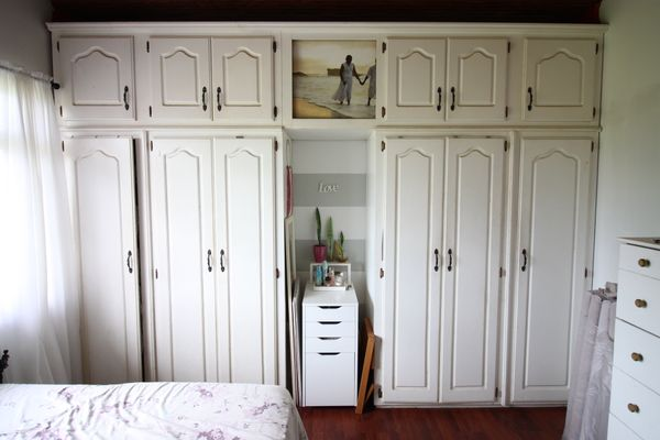 white wall-to-wall closet with nook in small bedroom